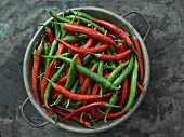Red and green chilli peppers in a metal bowl