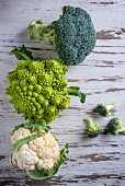 Cauliflower, romanesco and broccoli on a wooden background