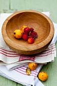 Decorated apples in a wooden bowl on kitchen towel