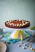 Chocolate tart for easter with easter eggs on a cake stand.