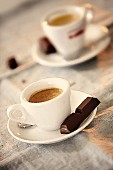 Two cups of espresso served with a piece of dark chocolate