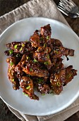 Asian-style sticky chicken wings sprinkled with sesame seeds and spring onions