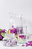 Glass jar of lilac flowers in sugar, glass and pitcher of lilac water with lemon and branch of fresh lilac