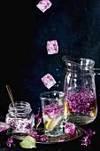 Fliederblüteneiswürfel fallen in Glas mit Fliederblütenlimonade