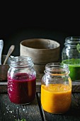 Assortment of vegetable smoothies from carrot, beetroot and spinach in glass jars