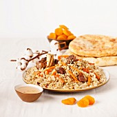 Uzbek national dish pilaf on plate with Uzbek bread and dried apricots