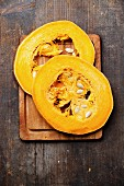 Cut a piece of ripe pumpkin on wooden background