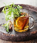 Tarragon hot drink tea with honey, lemon and cinnamon on dark background