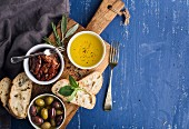 Mediterranean snacks set. Olives, oil, herbs and sliced ciabatta bread on yellow rustic oak board