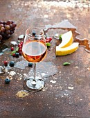 Glass of rose wine with berries, melon, grapes and ice on rusty metal background