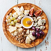 Cheese plate Assortment of various types of cheese on olive wood plate
