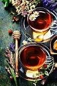 Kräutertee mit Honig, umgeben von Waldbeeren und Wiesenblumen