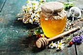 Stillleben mit Honig, Kräutertee und Blüten