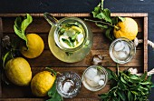 Homemade lemonade with mint and ice, served with fresh lemons over wooden tray surface