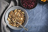 A bowl of quinoa crunch surrounded with pomegranate seeds and sliced apricots