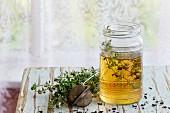 Kräutertee mit frischem Thymian serviert im Glas auf Vintage-Hocker