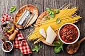Zutaten für Spaghetti Bolognese auf grauem Holzuntergrund