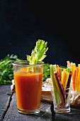Sliced colorful raw carrots and celery as vegetarian snack, and glass cup of fresh orange and carrot juice