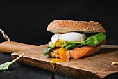 Bagel with salted salmon, spinach, avocado and soft boiled egg with liquid yolk on wooden chopping board