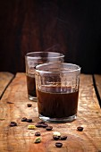 Coffee in glass and ingredients on wood background