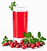 Fruit drink made from cranberries with leaves on white background