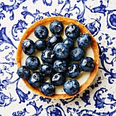 Blueberry tart on blue ornament background