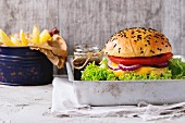 Fresh homemade burger with black sesame seeds in old aluminum tray with grilled potatoes