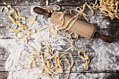 Top view on raw homemade pasta with flour and vintage rolling pin over old wooden table