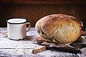 Fresh homemade bread on wooden cutting board with vintage knife and mug of milk