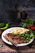 Grilled steak with potatoes and green salad on white ceramic plate and vintage glass with red wine over old wooden table