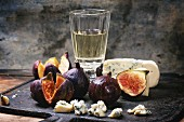 Figs with blue cheese, white wine and crackers on black cutting board