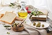 Grüne Oliven, Weissbrot und Olivenöl serviert mit Vintage Buch auf alten Holztisch