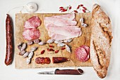 Wooden cutting board with set of ham and salami sausages with fresh bread and red hot chili peppers