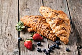 Two fresh croissant with berries over old wooden table