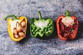Drei verschiedenfarbige, unterschiedlich gefüllte Paprikahälften