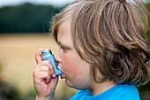 Child using asthma inhaler