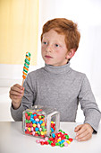 Boy holding lollipop with jar of sweets
