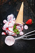 Wafer cone with strawberry ice cream with fresh strawberries, mint and metal spoon over black table