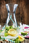 Glass pitcher of homemade lemonade with lemon, lime, sugar and mint on old wooden table