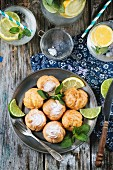 Vintage plate of homemade cakes profiteroles served with lemonade on old wooden table