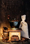 Stiill life with Antique coffee grinder, burlap sack, coffee cups and chocolate on rustic table