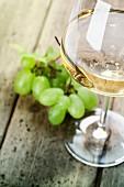 Ein Glas Weisswein und Trauben auf Holztisch