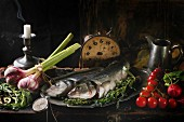 Still life with raw fish seabass, herbs, vegetables and vintage clock