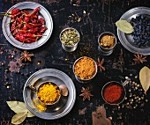 Set of spices pepper, turmeric, anise, coriander in vintage metal cups over old wooden table