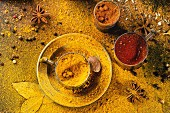 Set of spices pepper, turmeric, anise, coriander in vintage metal cups over yellow curry powder