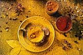 Verschiedene Gewürze Pfeffer, Kurkuma, Anis, Koriander in Vintage-Metallbecher, bestäubt mit gelbem Currypulver