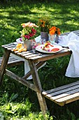 Summery table set for two with colourful posies in garden
