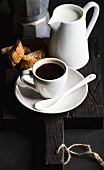 Italian coffee breakfat set: Cup of hot espresso, creamer with milk and cookies on dark wooden board