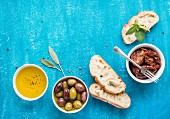 Pickled olives, oil, sun-dried tomatoes, herbs and sliced ciabatta bread over blue painted background