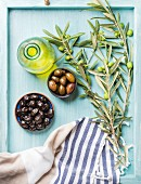 Two bowls with pickled green and black olives, olive tree sprigs, fresh homemade oil over blue Turquoise background